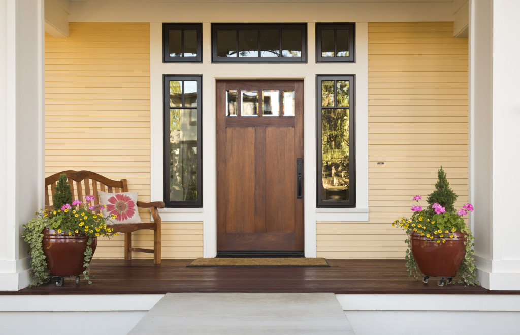 Front view of a wooden front door on a yellow house with reflections in the window and a wide view of the porch and front walkway.