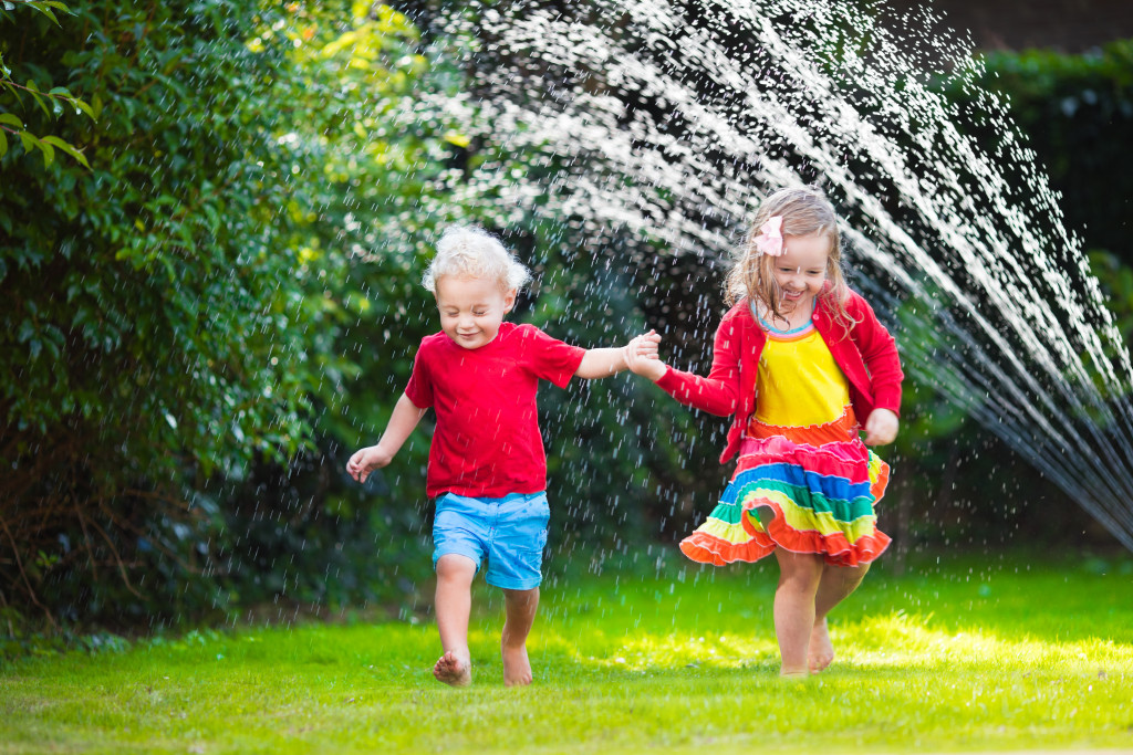 Child playing with garden sprinkler